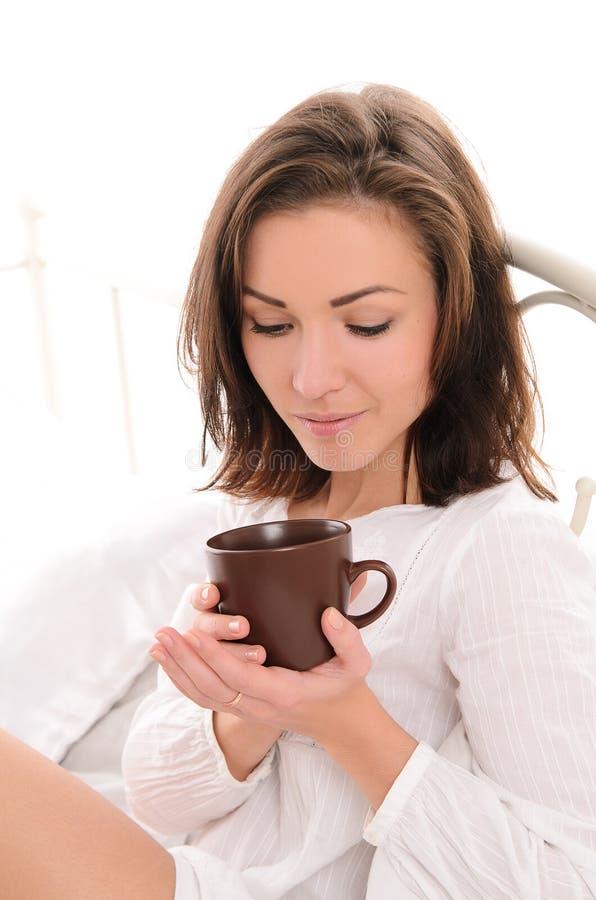 Νέα όμορφη γυναίκα με το φλιτζάνι του καφέ ή το τσάι στοκ εικόνες