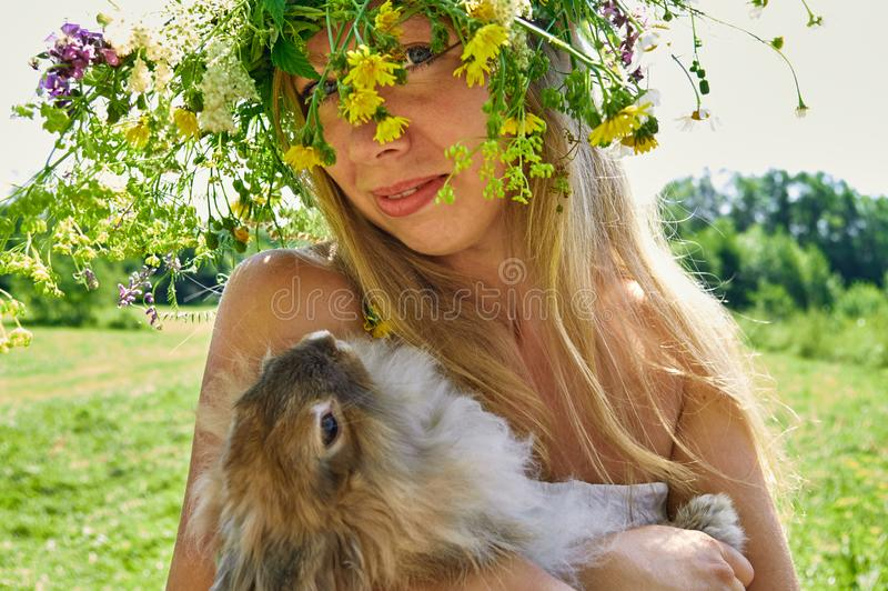 Νέα όμορφη γυναίκα με she's λατρευτό παραμονή κουνελιών κατοικίδιων ζώων ※ χαριτωμένη καφετιά στο λιβάδι στην ηλιόλουστη και  στοκ φωτογραφία