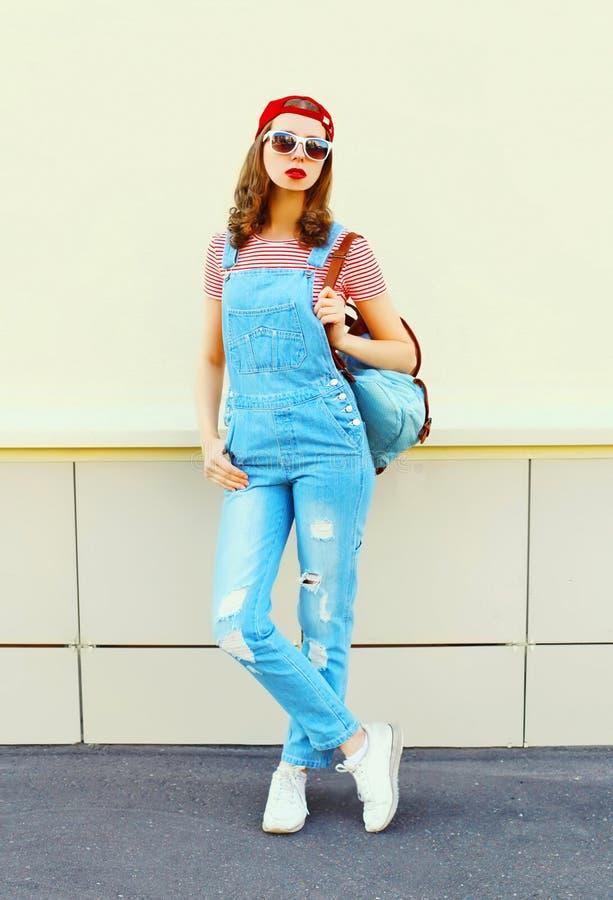 Νέα όμορφη γυναίκα μόδας που φορά ένα τζιν jumpsuit στην πόλη πέρα από το λευκό στοκ φωτογραφίες