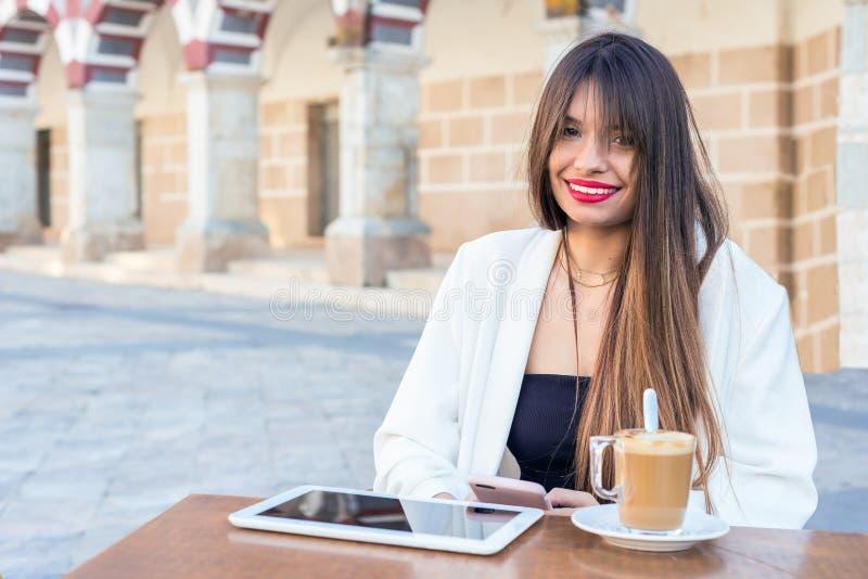 Νέα όμορφη γυναίκα που έχει έναν καφέ στοκ φωτογραφίες