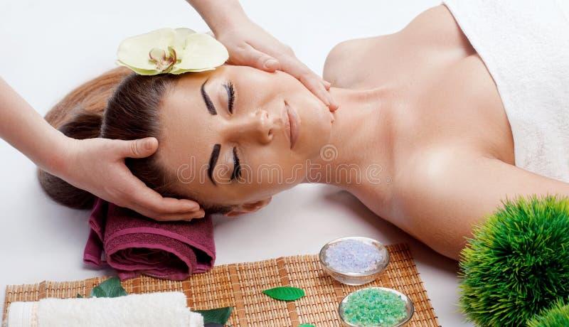 Νέα όμορφη γυναίκα που απολαμβάνει τη διαδικασία μασάζ προσώπου Χαλάρωση στοκ φωτογραφία με δικαίωμα ελεύθερης χρήσης