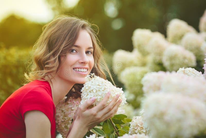 Νέα όμορφη γυναίκα που απολαμβάνει τη μυρωδιά των ανθίζοντας λουλουδιών στοκ εικόνες με δικαίωμα ελεύθερης χρήσης