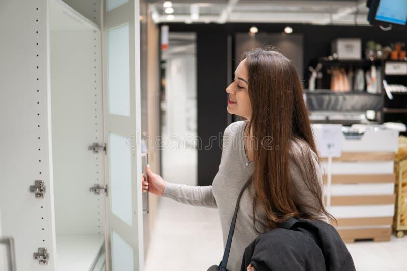 Νέα όμορφη γυναίκα που βρίσκεται νέα έπιπλα, ντουλάπα στοκ εικόνες
