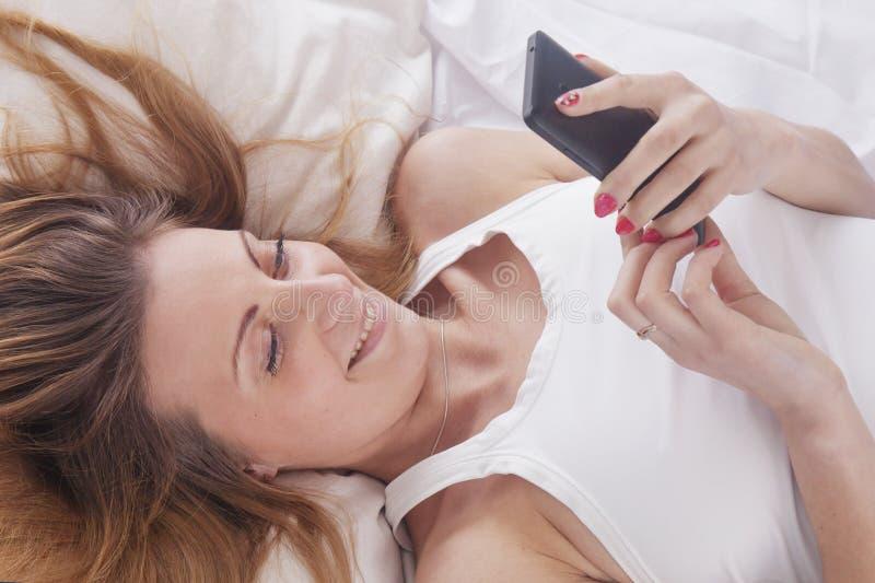 Νέα όμορφη γυναίκα που βρίσκεται στο κρεβάτι της και που χρησιμοποιεί το κινητό τηλέφωνο στοκ φωτογραφίες