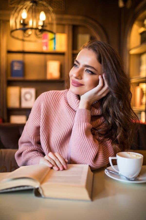 Νέα όμορφη γυναίκα που διαβάζει το ενδιαφέρον βιβλίο στον καφέ στοκ εικόνες