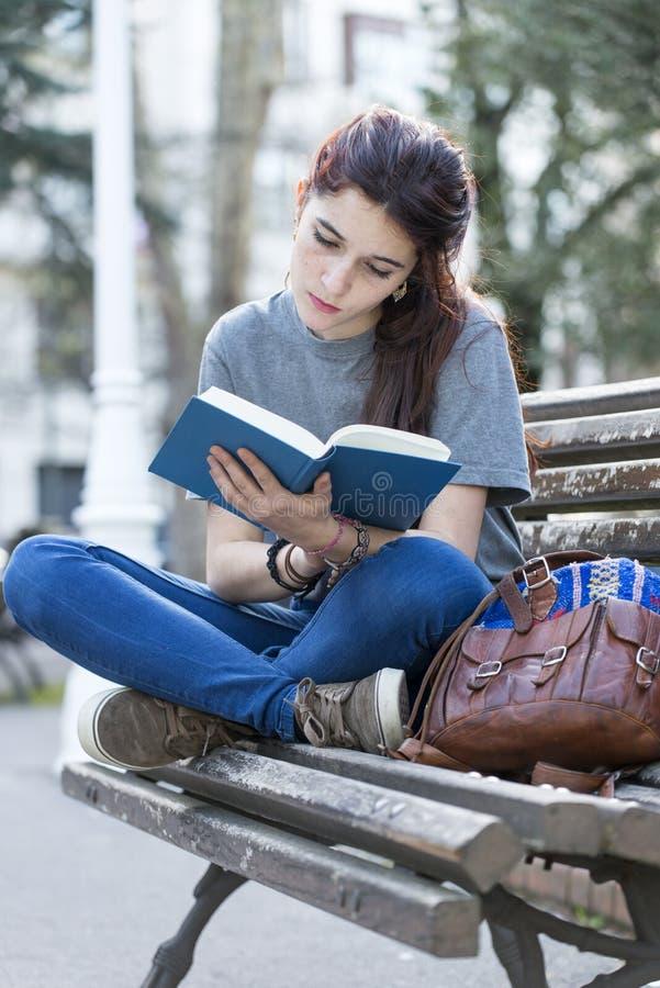 Νέα όμορφη γυναίκα που διαβάζει το μπλε βιβλίο στην οδό στοκ φωτογραφία