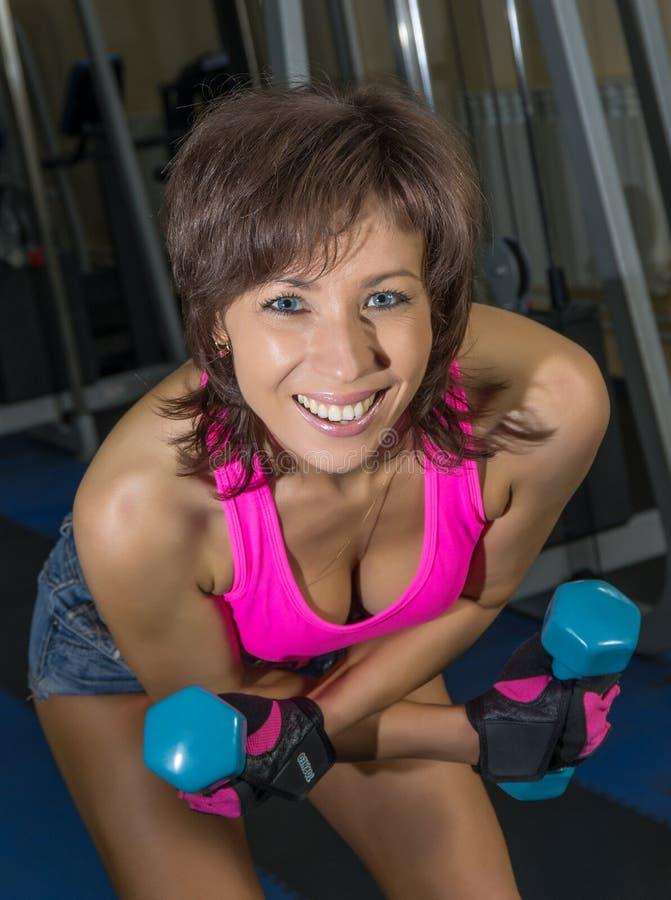 Νέα όμορφη γυναίκα που κάνει τις ασκήσεις με τους αλτήρες στοκ εικόνα