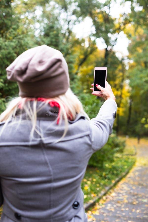 Νέα όμορφη γυναίκα που κάνει selfie έξω στο χρόνο πτώσης στοκ εικόνα με δικαίωμα ελεύθερης χρήσης