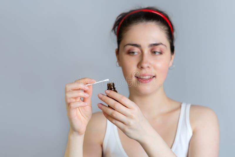 Νέα όμορφη γυναίκα που κρατά ένα βαμβάκι και ένα μπουκάλι ακτινικό φάρμακο Η έννοια της ακμής, της ενηλικίωσης και της καλλυντική στοκ φωτογραφίες με δικαίωμα ελεύθερης χρήσης