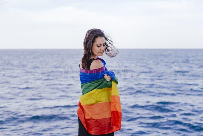 Νέα όμορφη γυναίκα που κρατά μια ομοφυλοφιλική σημαία ουράνιων τόξων υπαίθρια ΤΡΟΠΟΣ ΖΩΉΣ μια έννοια υπερηφάνειας η αγάπη είναι α στοκ φωτογραφίες