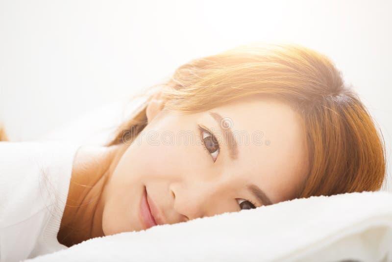 Νέα όμορφη γυναίκα που ξυπνά στο κρεβάτι στοκ εικόνες