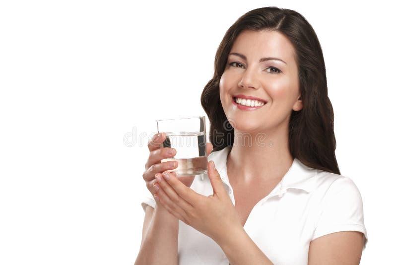 Νέα όμορφη γυναίκα που πίνει ένα ποτήρι του νερού στοκ εικόνες