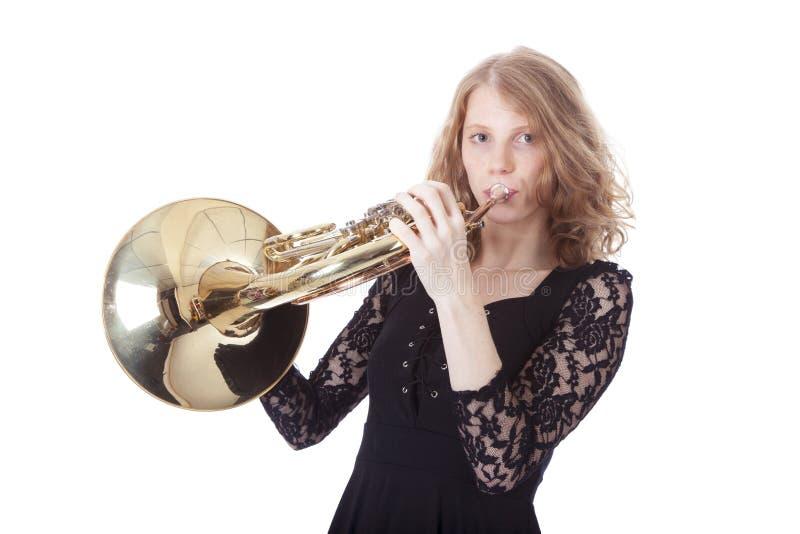 Νέα όμορφη γυναίκα που παίζει το γαλλικό κέρατο στοκ εικόνες