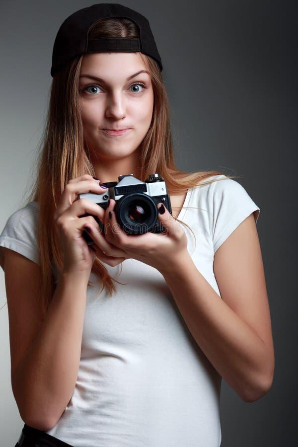 Νέα όμορφη γυναίκα που παίρνει μια φωτογραφία με μια αναδρομική κάμερα στοκ εικόνες
