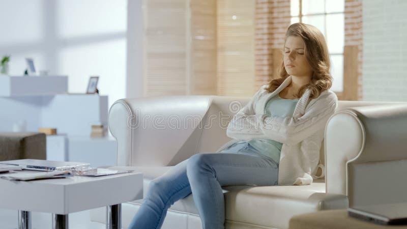 Νέα όμορφη γυναίκα που παίρνει το NAP στον καναπέ, υπόλοιπο στα μέσα της ημέρας, χαλάρωση στοκ φωτογραφία με δικαίωμα ελεύθερης χρήσης