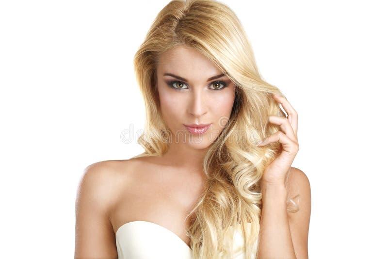 Νέα όμορφη γυναίκα που παρουσιάζει ξανθή τρίχα της στοκ φωτογραφία
