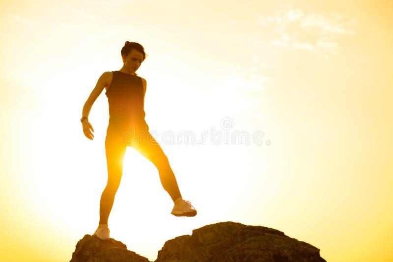 Νέα όμορφη γυναίκα που περπατά στους βράχους στα βουνά στο θερινό ηλιοβασίλεμα r στοκ φωτογραφίες με δικαίωμα ελεύθερης χρήσης