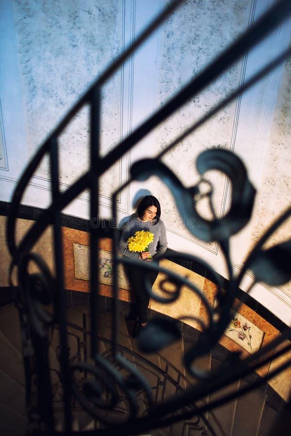 Νέα όμορφη γυναίκα που στέκεται στην παλαιά στρογγυλή σπειροειδή σκάλα Τοπ όψη στοκ φωτογραφία