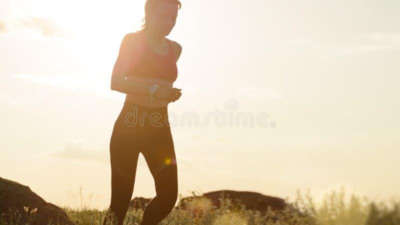 Νέα όμορφη γυναίκα που τρέχει στο ίχνος βουνών στο καυτό θερινό ηλιοβασίλεμα Αθλητισμός και ενεργός τρόπος ζωής στοκ φωτογραφίες