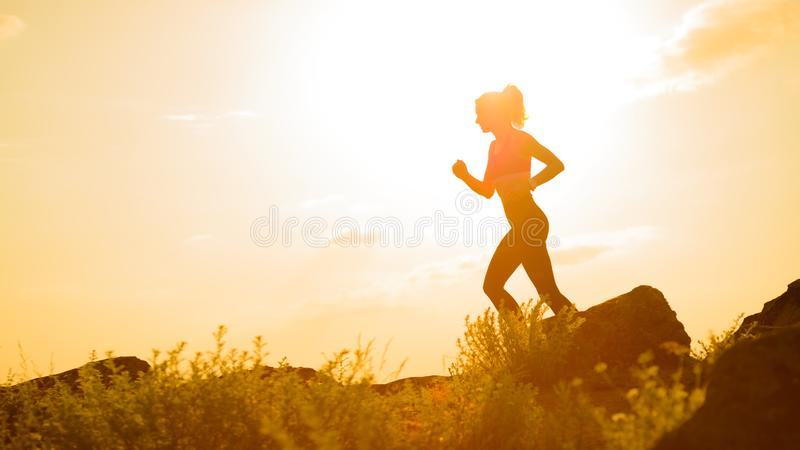 Νέα όμορφη γυναίκα που τρέχει στο ίχνος βουνών στο καυτό θερινό ηλιοβασίλεμα Αθλητισμός και ενεργός τρόπος ζωής στοκ φωτογραφίες με δικαίωμα ελεύθερης χρήσης