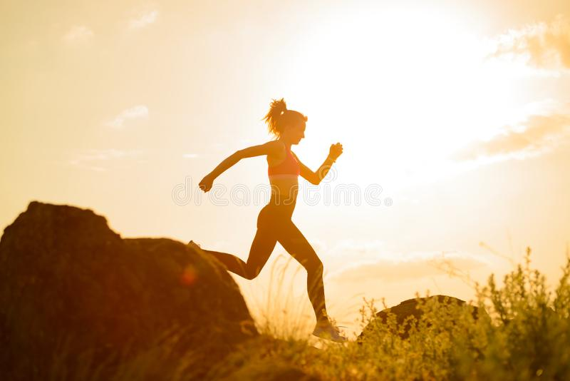 Νέα όμορφη γυναίκα που τρέχει στο ίχνος βουνών στο καυτό θερινό ηλιοβασίλεμα Αθλητισμός και ενεργός τρόπος ζωής στοκ εικόνα με δικαίωμα ελεύθερης χρήσης