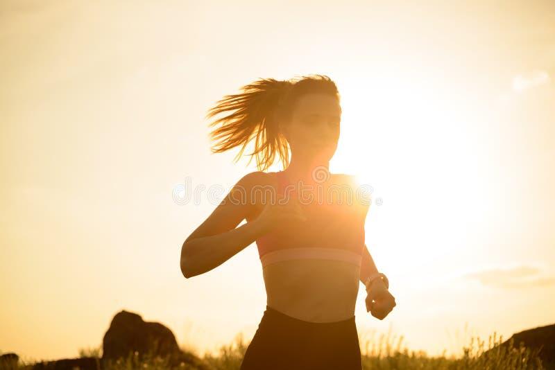 Νέα όμορφη γυναίκα που τρέχει στο ίχνος βουνών στο καυτό θερινό ηλιοβασίλεμα Αθλητισμός και ενεργός τρόπος ζωής στοκ φωτογραφία με δικαίωμα ελεύθερης χρήσης