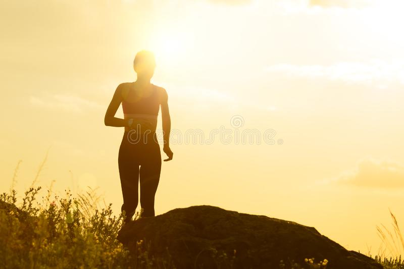 Νέα όμορφη γυναίκα που τρέχει στο ίχνος βουνών στο καυτό θερινό ηλιοβασίλεμα Αθλητισμός και ενεργός τρόπος ζωής στοκ εικόνες