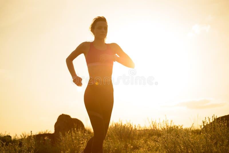 Νέα όμορφη γυναίκα που τρέχει στο ίχνος βουνών στο καυτό θερινό ηλιοβασίλεμα Αθλητισμός και ενεργός τρόπος ζωής στοκ εικόνα