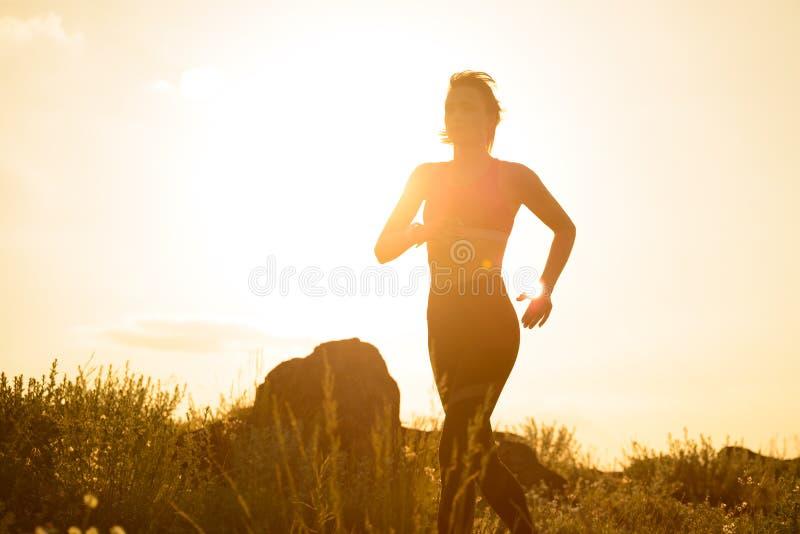 Νέα όμορφη γυναίκα που τρέχει στο ίχνος βουνών στο καυτό θερινό ηλιοβασίλεμα Αθλητισμός και ενεργός τρόπος ζωής στοκ εικόνες με δικαίωμα ελεύθερης χρήσης