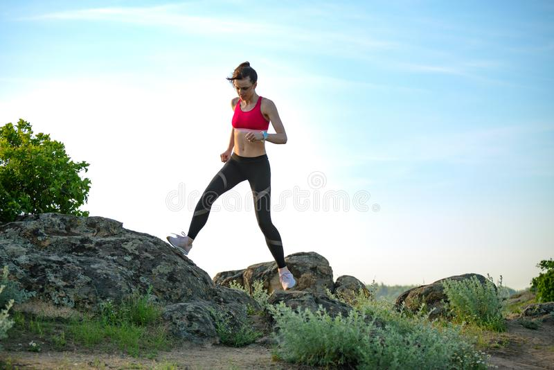 Νέα όμορφη γυναίκα που τρέχει στο ίχνος βουνών το καυτό θερινό βράδυ Αθλητισμός και ενεργός τρόπος ζωής στοκ φωτογραφία