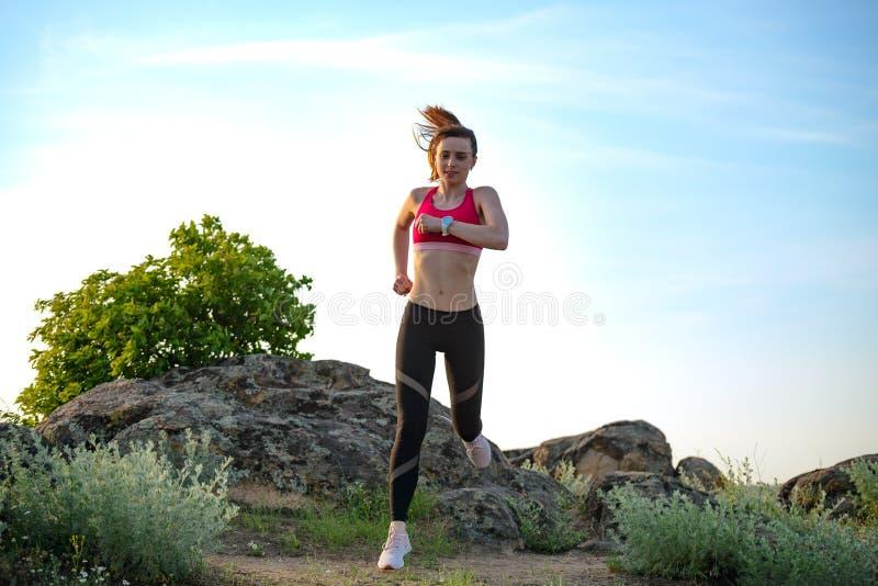 Νέα όμορφη γυναίκα που τρέχει στο ίχνος βουνών το καυτό θερινό βράδυ Αθλητισμός και ενεργός τρόπος ζωής στοκ εικόνες με δικαίωμα ελεύθερης χρήσης