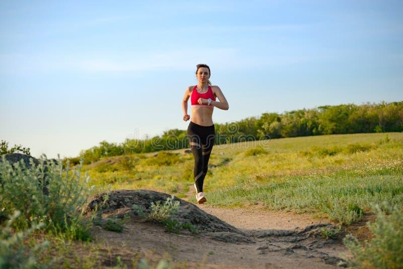 Νέα όμορφη γυναίκα που τρέχει στο ίχνος βουνών το καυτό θερινό βράδυ Αθλητισμός και ενεργός τρόπος ζωής στοκ φωτογραφίες