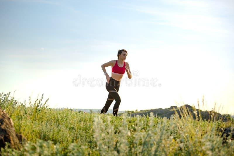 Νέα όμορφη γυναίκα που τρέχει στο ίχνος βουνών το καυτό θερινό βράδυ Αθλητισμός και ενεργός τρόπος ζωής στοκ εικόνα