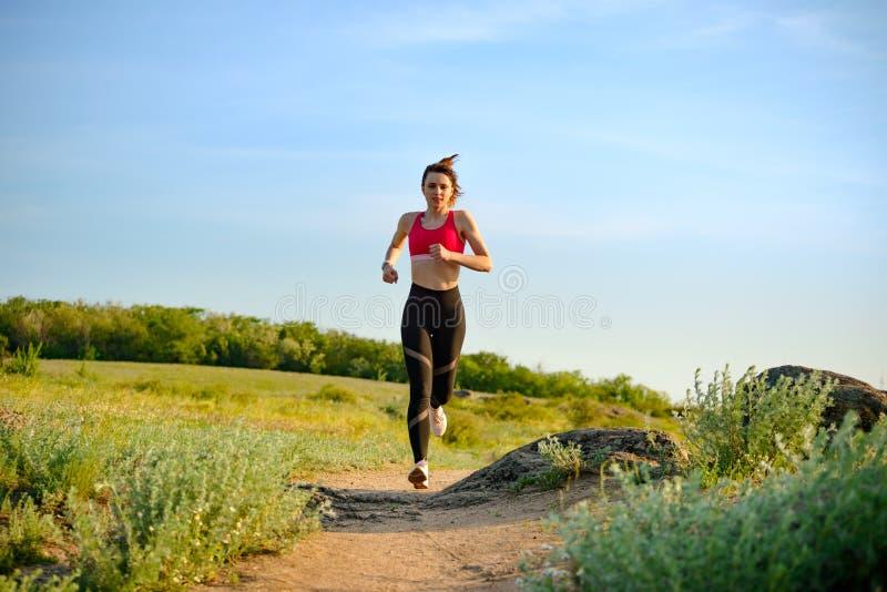 Νέα όμορφη γυναίκα που τρέχει στο ίχνος βουνών το καυτό θερινό βράδυ Αθλητισμός και ενεργός τρόπος ζωής στοκ φωτογραφία με δικαίωμα ελεύθερης χρήσης