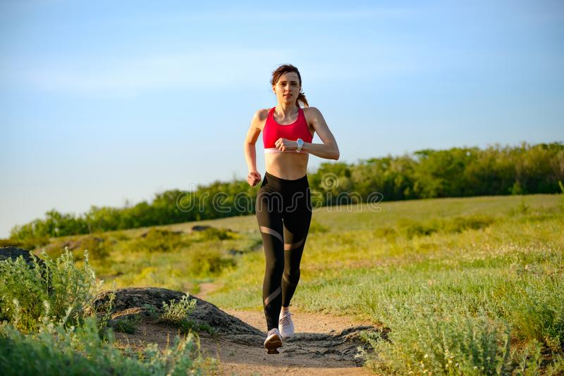 Νέα όμορφη γυναίκα που τρέχει στο ίχνος βουνών το καυτό θερινό βράδυ Αθλητισμός και ενεργός τρόπος ζωής στοκ εικόνα με δικαίωμα ελεύθερης χρήσης