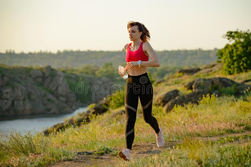 Νέα όμορφη γυναίκα που τρέχει στο ίχνος βουνών το καυτό θερινό βράδυ Αθλητισμός και ενεργός τρόπος ζωής στοκ εικόνες