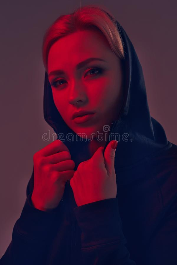 Νέα όμορφη γυναίκα που φορά μια μαύρη κουκούλα και τα σορτς στο σκοτεινό υπόβαθρο Πορτρέτο στοκ εικόνες με δικαίωμα ελεύθερης χρήσης