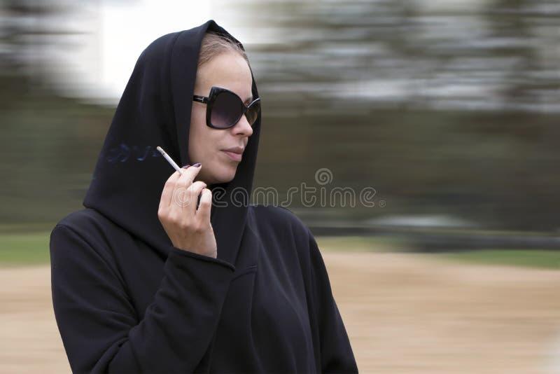 Νέα όμορφη γυναίκα που φορά τη μαύρα κουκούλα και τα γυαλιά ηλίου με το τσιγάρο διαθέσιμο στοκ εικόνα με δικαίωμα ελεύθερης χρήσης