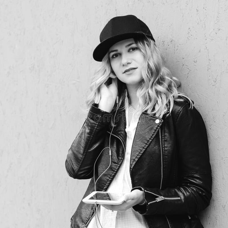 Νέα όμορφη γυναίκα που φορά τη μοντέρνη εξάρτηση ύφους Κορίτσι Hipster που χαλαρώνουν και μουσική ακούσματος υπαίθρια Μουσική ακο στοκ φωτογραφίες