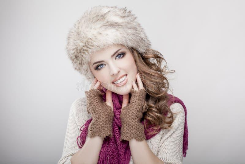 Νέα όμορφη γυναίκα που φορά το καπέλο και το μαντίλι γουνών στοκ εικόνα