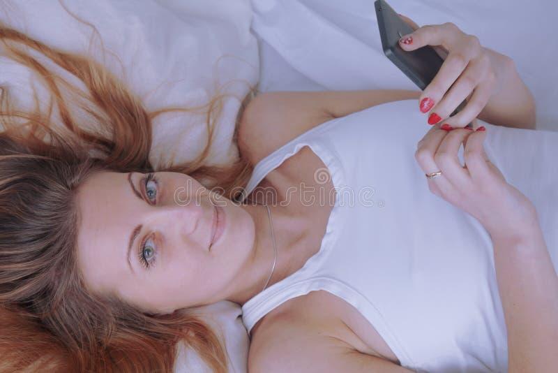 Νέα όμορφη γυναίκα που χαλαρώνει και που παίζει το κινητό τηλέφωνο στο κρεβάτι στοκ εικόνες