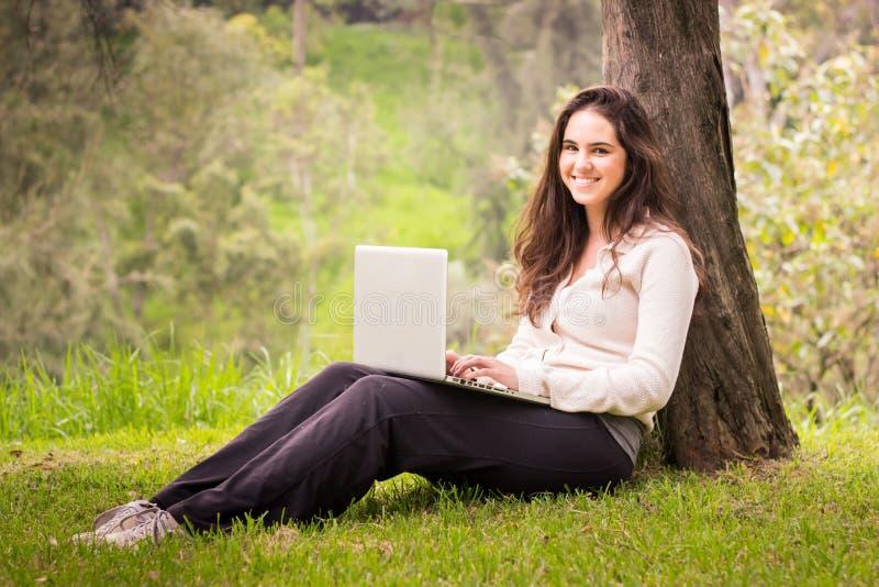 Νέα όμορφη γυναίκα που χρησιμοποιεί έναν φορητό προσωπικό υπολογιστή στο πάρκο στοκ φωτογραφία με δικαίωμα ελεύθερης χρήσης