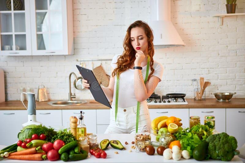 Νέα όμορφη γυναίκα που χρησιμοποιεί την ταμπλέτα μαγειρεύοντας στη σύγχρονη κουζίνα Υγιής κατανάλωση, βιταμίνες, να κάνει δίαιτα, στοκ εικόνα με δικαίωμα ελεύθερης χρήσης