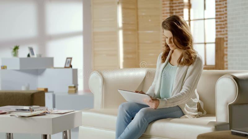 Νέα όμορφη γυναίκα που ψωνίζει on-line στην ταμπλέτα, που διατάζει τα αγαθά, ηλεκτρονικό εμπόριο στοκ εικόνες