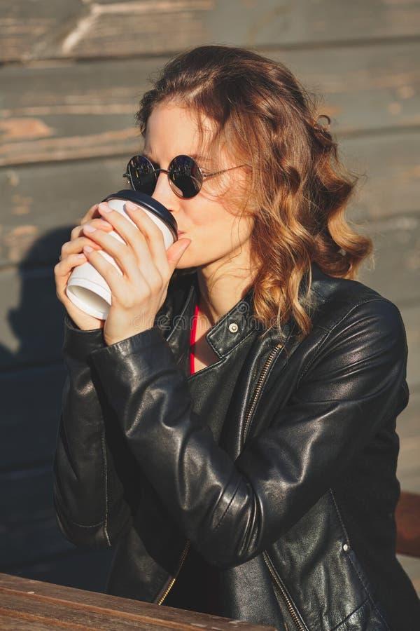 Νέα όμορφη γυναίκα σε έναν μαύρο καφέ κατανάλωσης σακακιών δέρματος στοκ φωτογραφία με δικαίωμα ελεύθερης χρήσης