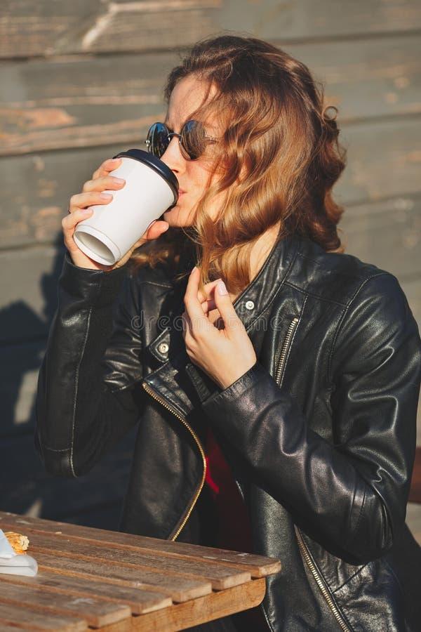 Νέα όμορφη γυναίκα σε έναν μαύρο καφέ κατανάλωσης σακακιών δέρματος στοκ εικόνες