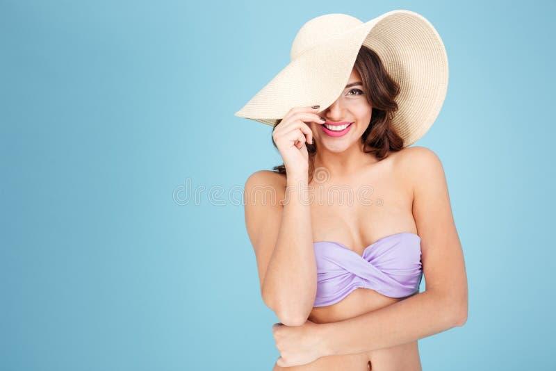 Νέα όμορφη γυναίκα σε ένα καπέλο και ένα μαγιό παραλιών στοκ φωτογραφία
