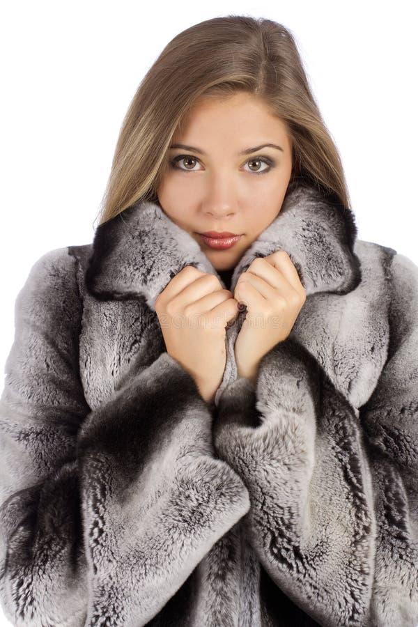 Νέα όμορφη γυναίκα σε ένα παλτό γουνών στο σχεδιάγραμμα στοκ εικόνες