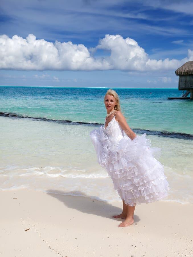 Νέα όμορφη γυναίκα σε μια μόνιμη εν πλω άκρη φορεμάτων νυφών στοκ εικόνες