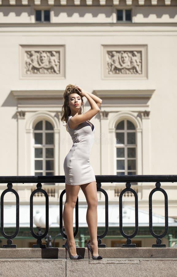 Νέα όμορφη γυναίκα στην μπεζ σύντομη τοποθέτηση φορεμάτων υπαίθρια στο SU στοκ φωτογραφίες με δικαίωμα ελεύθερης χρήσης